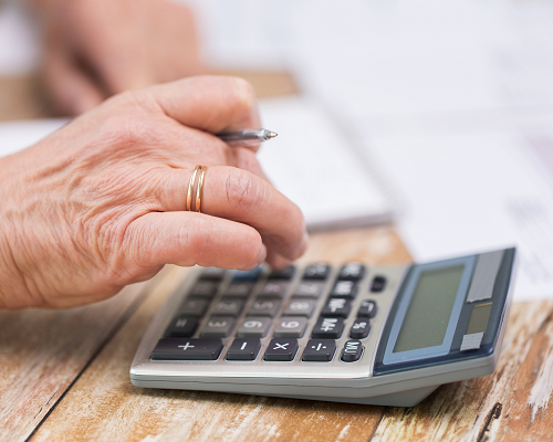 Close up of senior woman's hand with calculator