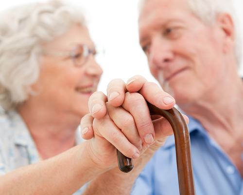 Senior couple holding hands on top of a cane