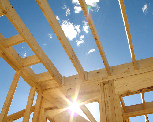 Wood framing of a home with a bright blue sky behind it