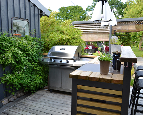 Outdoor kitchen with stainless steel grill and bar seating