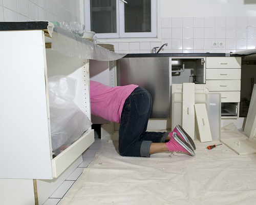 Woman kneeling to reface cabinets