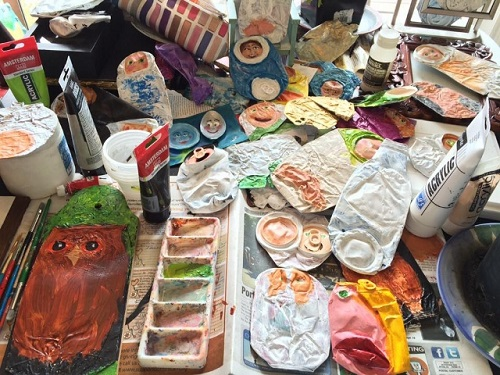 Work table showing supplies for making crushed can art