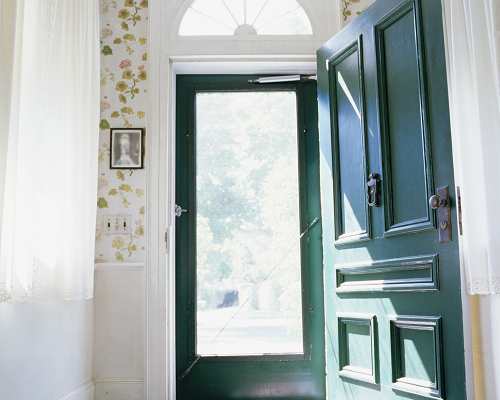 Interior shot of an open green front door