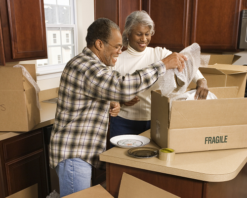 Senior couple packing boxes to move